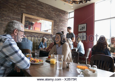 Grandfather and teenage granddaughter talking, eating brunch at diner table - Stock Photo