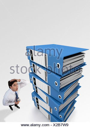 Businessman tensed after looking at a stack of files - Stock Photo