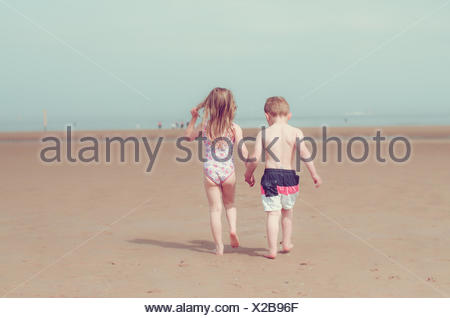 Girl and boy holding hands and walking on beach - Stock Photo