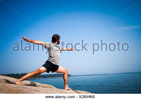 Man doing warrior yoga pose on beach, Maine, America, USA - Stock Photo