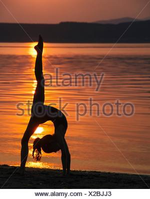 Side view of girl in silhouette by ocean at sunset bending over backwards leg raised doing the splits - Stock Photo