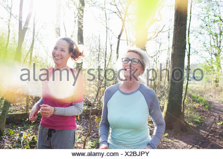 Women jogging in forest smiling - Stock Photo