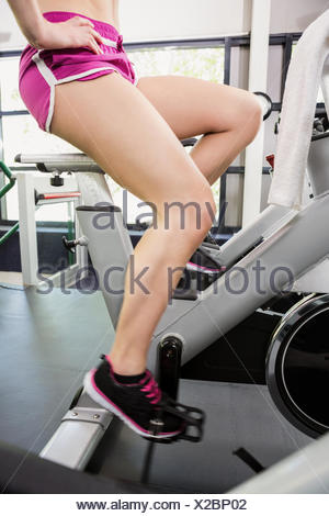 Woman working out on exercise bike at spinning class - Stock Photo