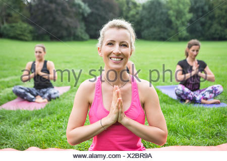 Young women practicing yoga in park hands folded - Stock Photo