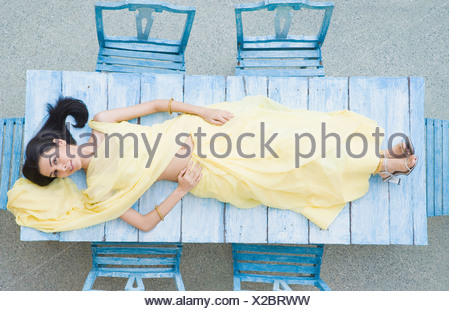 High angle view of a young woman lying on a table and smiling - Stock Photo