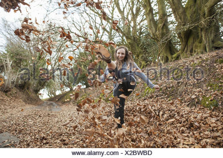 Young woman playing in fallen leaves, kicking them in the air. - Stock Photo