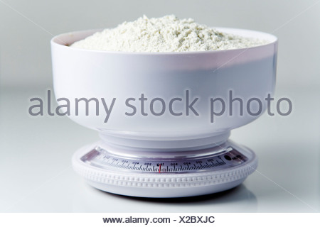 Flour in a kitchen scale - Stock Photo