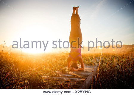 Mid adult woman doing morning yoga in a field, Upper Herring Lake Nature Preserve, Frankfort, Benzie County, Michigan, USA - Stock Photo