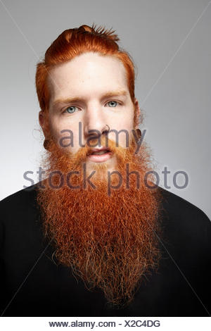 Studio portrait of staring young man with red hair and overgrown beard - Stock Photo
