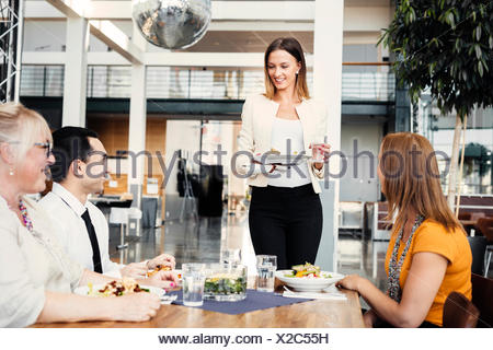 Four colleagues meeting over lunch in cafeteria - Stock Photo
