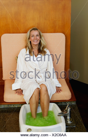 Portrait of a mature woman getting pedicure - Stock Photo