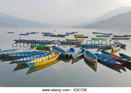 Colorful boats on Phewa Lake, hills and clouds in the back, Pokhara, Nepal - Stock Photo