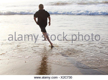 Rear view of boy running in surf on beach - Stock Photo