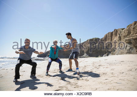 Crossfit trainer helping senior couple exercising, doing squats on sunny beach - Stock Photo