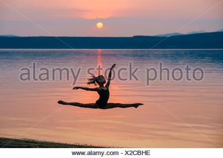 Side view of girl by ocean at sunset leaping in mid air, arms raised doing the splits - Stock Photo