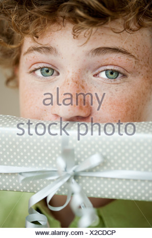 Boy holding gift in front of mouth, portrait - Stock Photo