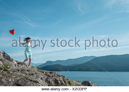 Mature woman pulling heart shaped balloon, Vancouver, Canada - Stock Photo