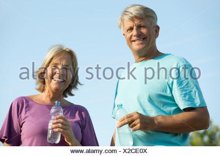 Senior couple holding bottles of water, portrait - Stock Photo