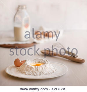 Baking ingredients and tools on light, natural background. - Stock Photo