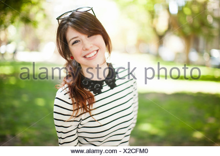 Portrait of young woman in park - Stock Photo