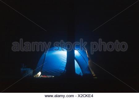 Blue Illuminated Dome Tent On Field At Night - Stock Photo