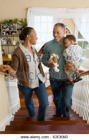 Grandparents carrying their grandson upstairs - Stock Photo