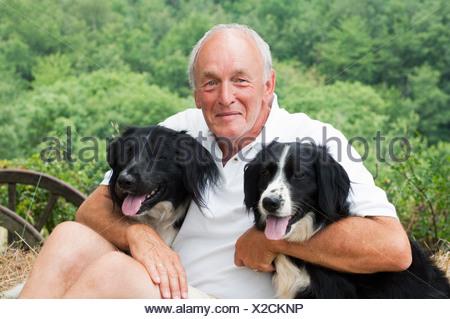 Senior man holding two dogs, portrait - Stock Photo