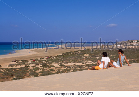 A couple sitting on a sand dune overlooking the Playas de Sotavento beach, Fuerteventura, Canary Islands, Spain, Europe - Stock Photo