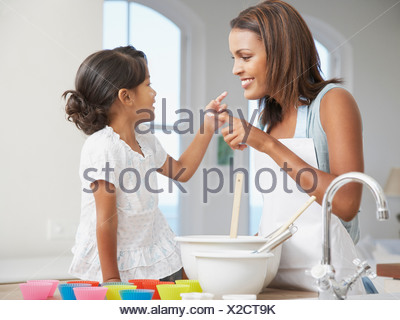 Mother and daughter baking cupcakes in kitchen - Stock Photo