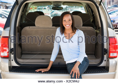 Woman sitting in back of van smiling - Stock Photo