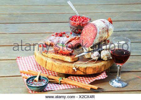 Salami on chopping board with wine and condiments - Stock Photo