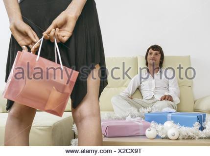 Paar, Mann sitzt auf Sofa, Frau steht mit Geschenktuete davor (model-released) - Stock Photo