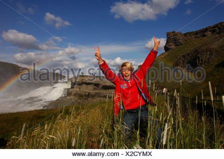 Child jubilating under rainbow on Gullfoss, The Golden Waterfall, Iceland, Europe - Stock Photo