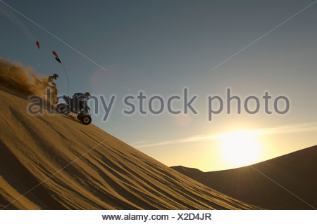 Men riding quad bikes in desert at sunset Stock Photo