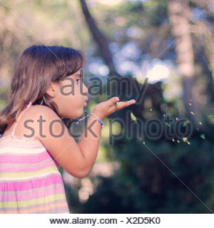 Girl (6-7) blowing leaves from hand - Stock Photo