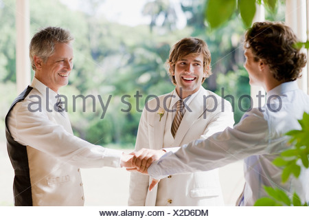 Groomsmen at wedding holding hands - Stock Photo