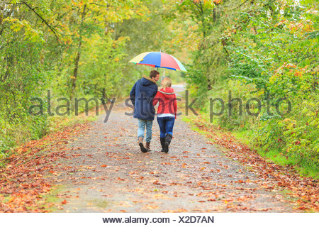 Young couple strolling along country lane with colorful umbrella - Stock Photo
