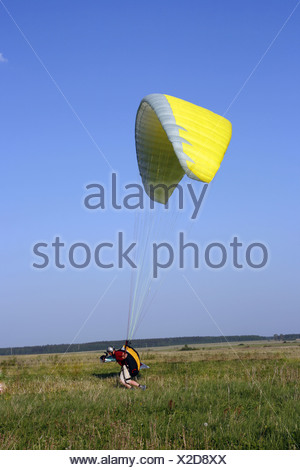 Paraglider landing with yellow wing - Stock Photo
