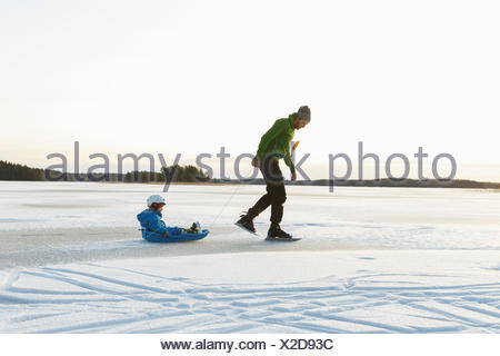 Sweden, Sodermanland, Jarna, Father with son (2-3) tobogganing - Stock Photo