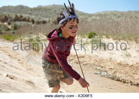 Young boy, wearing fancy dress, running on sand - Stock Photo