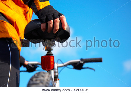 Young person holding mountain bike, Lake District National Park, Cumbria, UK - Stock Photo