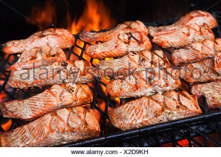 Slices of salmon being grilled over an open fire pit at Gold Creek Salmon Bake, Juneau, Alaska, U.S.A. - Stock Photo
