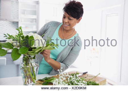 Middle-aged woman arranging flowers in vase - Stock Photo