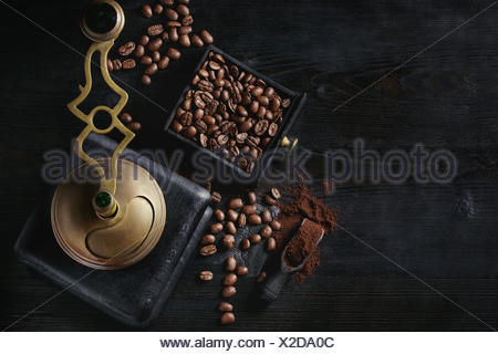 Roasted coffee beans and grind coffee in wood box with vintage coffee grinder and scoop over black wooden burnt background. Top view with space. - Stock Photo