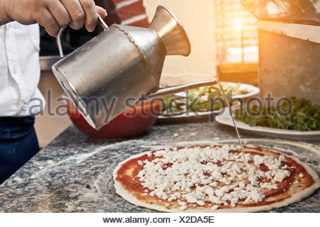 Chef pouring oil on uncooked pizza - Stock Photo