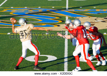 American football quarterback attempting to throw ball as opposing players close in during competitive game, side view - Stock Photo