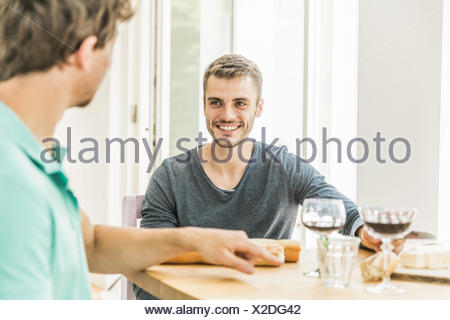 Two young men chatting at table at party in dining room - Stock Photo