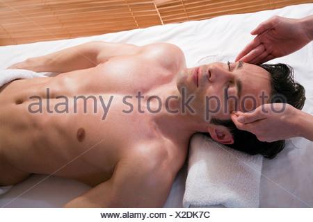 Wellness: man receiving facial massage - Stock Photo