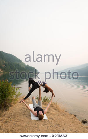 Fit couple practicing acro yoga in a lush green ground - Stock Photo