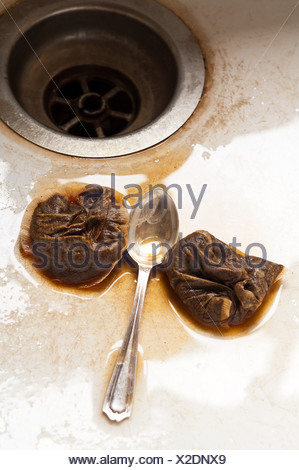 Teaspoon and teabags in kitchen sink - Stock Photo